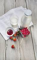 Milchflasche, Milchglas, Marmelade und Erdbeeren mit Leinentuch