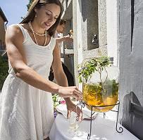 Frau im weißen Kleid zapft selbstgemachte Limonade