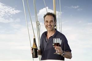 Mann erwartungsvoll mit zwei Weingläsern und Weinflasche in der