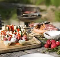 Fleisch, Wurst und Grillspieße draußen vorbereitet