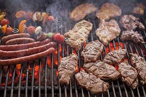 Mit Fleisch, Würsten und Spießen belegter Kohlegrill