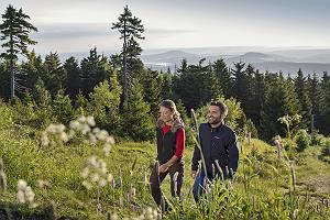 Paar wandert auf dem Fichtelberg im Erzgebirge mit Bergpanorama
