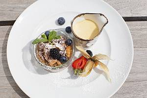 Dessert aus Souffle im Glas mit Vanillesoße und Beeren und Minz
