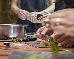 Händen beim würzen und Anrichten mehrerer Personen beim Kochen