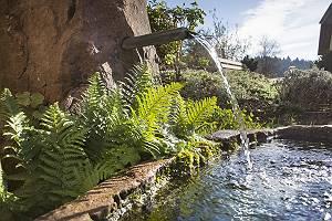 Brunnen aus Stein mit fließendem Wasser welchessich in einem St