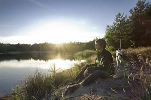 Junger Mann sitzt in der Abendsonne am Ufer eines Sees