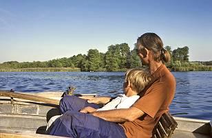 Vater und Sohne aneinander angelehnt sitzen in einem Ruderboot u