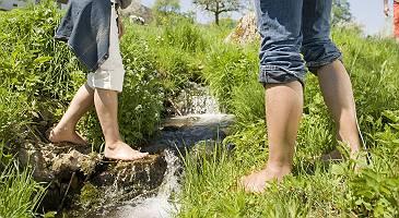 Füße eines Mannes und einer Frau erfrischen Ihre Füße an ein