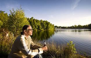 Mann genießt sein Bier am See in der Abendsonne im Gegegenlicht