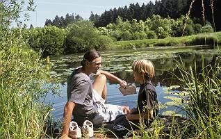 Naturerfahrung von Vater und Sohn sich zugewandt auf einem Steg