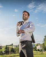 Optimistischer junger Mann in Hemd lächelt und setzt einen Wür