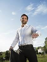 Optimistischer junger Mann in Hemd strahlt und setzt einen Würf