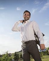 Junger Mann in Hemd wirft zuversichtlich seine Jacke zurück und