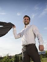 Junger unternehmungslustiger Mann in Hemd wirft zuversichtlich s