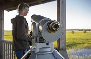 Fernrohr auf einem Aussichtsturm mit Mann im Hintergrund in der