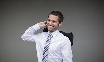 Mann in Hemd mit Krawatte wirft zuversichtlich seine Jacke zurü