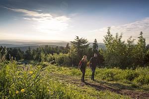 Paar wandert auf dem Fichtelberg im Erzgebirge im Gegenlicht