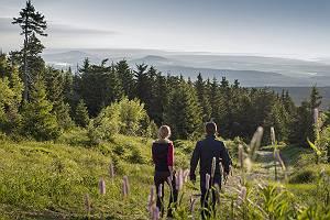 Paar wandert auf dem Fichtelberg im Erzgebirge mit Blick über d