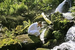 Mann der im Bademantel auf einem Felsen sitzt und sich an einem