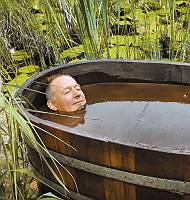 Mann genießt Moorbad dem natürlichen Heilmittel Moor, in einer