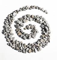 Spirale aus Steinen gelegt auf weißem Untergrund symbolisiert d