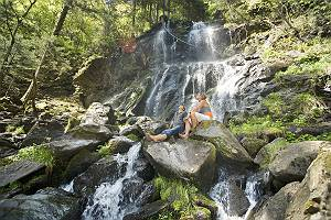 Paar sitzt auf Felsen vor einem Wasserfall und genießt die anre