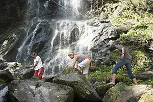 Drei Personen in sommerlicher Freizeitkleidung steigen über die