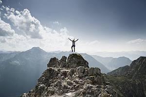 Ein Mann, der auf der Spitze eines Berges in die Luft springt