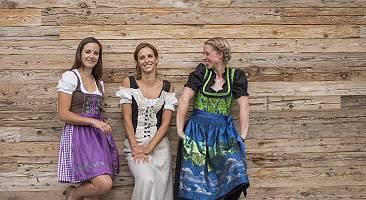 Drei Frauen stehen in Tracht vor einer Holzwand