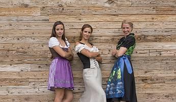Drei kesse Frauen stehen in Tracht vor einer Holzwand