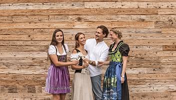 Sekt anstoßen Gruppe in Tracht vor einer Holzwand