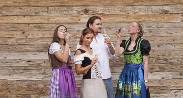 Sekt trinkende Personen in Tracht vor einer Holzwand