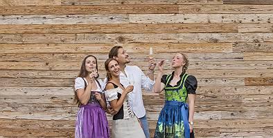 Personen in Tracht vor einer Holzwand Sekt trinkend