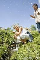 Fotografie einer Frau, die ihren Mann mit dem Wasser eines Bache