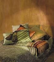 Schön hergerichtetes Bett mit farbigen Kissen und Decken