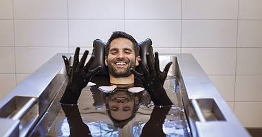 Mann streckt seine mit Moor bedeckten Hände aus dem Moorbad