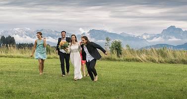 Hochzeitspaar rennt durch eine Wiese