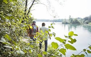 Älteres Paar geht entlang eines Sees spazieren