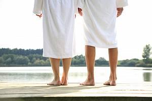 Paar im Bademantel barfuß am See