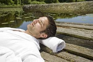 Mann liegt im Bademantel auf Holzsteg am See