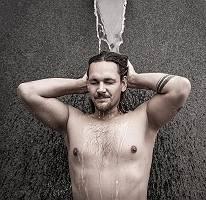 Kräftiger junger Mann beim Duschen