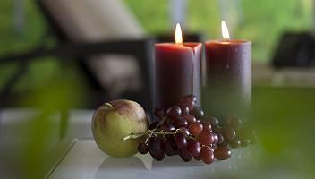 Zwei rote Kerzen, Trauben und ein Apfel