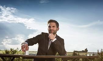 Mann im Anzug, angelehnt an ein Geländer