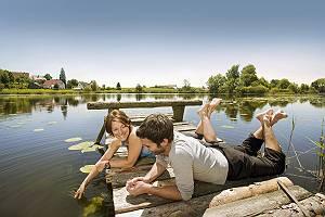 Paar auf Steg am See liegend