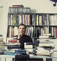Belesener Mann sitzt hinter vielen Büchern