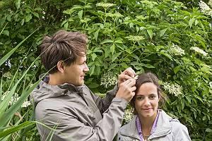 Mann steckt seiner Partnerin eine Holunderblüte ins Haar