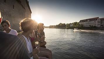 Junge Leute genießen bei einem Glas Sekt die Abendstimmung an d