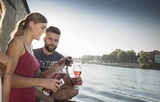 Paar genießt bei einem Glas Wein den Feierabend an der Donau in