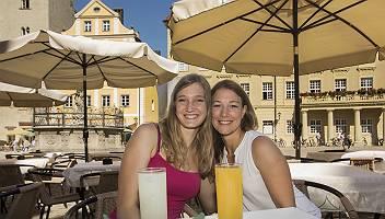 Zwei junge Frauen sitzen auf der Terrasse eines Restaurants in R