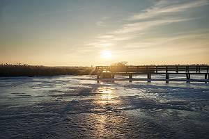 Gefrorener See mit Holzsteg im Sonnenuntergang